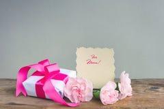 照顾` s天背景,礼物盒,三支桃红色康乃馨 库存照片