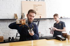 煮新鲜的咖啡的男性侍酒者在咖啡馆内部 免版税库存照片
