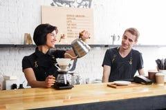 煮新鲜的咖啡的男性和女性侍酒者在咖啡馆内部 库存图片
