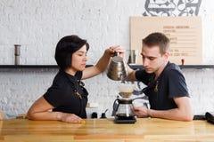 煮新鲜的咖啡的男性和女性侍酒者在咖啡馆内部 免版税库存图片