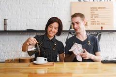 煮新鲜的咖啡的男性和女性侍酒者在咖啡馆内部 免版税库存照片