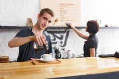 煮新鲜的咖啡的男性和女性侍酒者在咖啡馆内部 库存照片