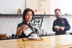 煮新鲜的咖啡的男性和女性侍酒者在咖啡馆内部 免版税图库摄影