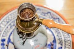 煮沸在便携式的火炉的土耳其咖啡罐 库存图片