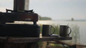 煮沸在煤气炉的早晨,在有美好的太阳强光的一个湖附近对此 HD 免版税图库摄影