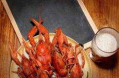 煮沸的小龙虾、杯低度黄啤酒和在一张木桌上的黑黑板 顶视图图片 库存照片
