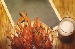 煮沸的小龙虾、杯低度黄啤酒和在一张木桌上的黑黑板 免版税库存照片
