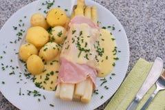 煮沸的白色芦笋用火腿和新鲜的新的煮的土豆服务用蛋黄奶油酸辣酱调味汁 库存图片