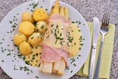 煮沸的白色芦笋用火腿和新鲜的新的煮的土豆服务用蛋黄奶油酸辣酱调味汁 库存照片