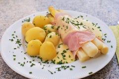 煮沸的白色芦笋用火腿和新鲜的新的煮的土豆服务用蛋黄奶油酸辣酱调味汁 免版税库存图片