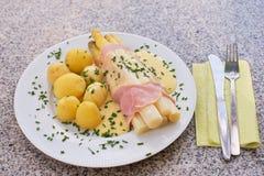 煮沸的白色芦笋用火腿和新鲜的新的煮的土豆服务用蛋黄奶油酸辣酱调味汁 图库摄影
