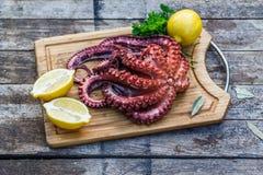 煮沸的章鱼准备好服务用柠檬和荷兰芹在木板 免版税库存图片