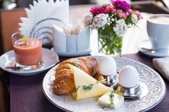 煮沸的蛋、新月形面包和草莓圆滑的人 库存照片