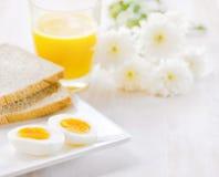煮沸的鸡蛋、多士和橙汁 免版税库存图片