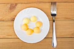 煮沸的鸡蛋卵黄质在白色板材和叉子的 免版税图库摄影