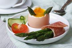 煮沸的鸡蛋用绿色芦笋、火腿和菜特写镜头 库存图片