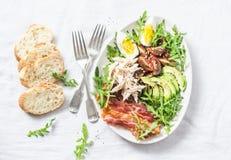 煮沸的鸡,鲕梨,鸡蛋,芝麻菜,蕃茄,在轻的背景的烟肉沙拉 免版税库存图片