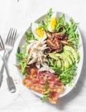 煮沸的鸡,鲕梨,鸡蛋,芝麻菜, kumato蕃茄,在轻的背景的烟肉沙拉 免版税库存照片