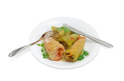 煮熟的圆白菜卷、叉子和刀子在白色盘 免版税图库摄影