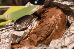 煮熟的猪肉内圆角,休息在烹调箔在厨房里 免版税库存照片