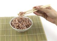 煮熟的红色米得到夹紧由筷子 库存图片