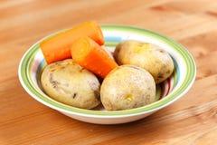 煮熟的红萝卜和土豆的菜混合在碗 免版税图库摄影