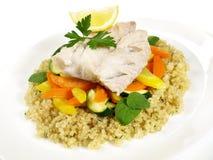 煮熟的绿鳕鱼用奎奴亚藜 库存图片