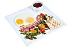 煮熟的英式早餐,煎蛋用在方形的普拉特的烟肉 免版税库存图片