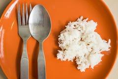 煮熟的茉莉花米在橙色板材的碳水化合物上是浓有匙子的,并且叉子在桌被安置并且准备 库存照片
