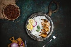 煮熟的虾用柠檬和葱在土气金属盘子有米配菜的在黑暗的桌上 免版税库存图片