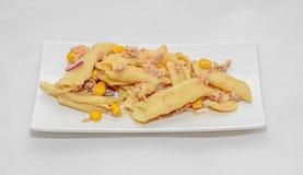 煮熟的面团用红洋葱、金枪鱼和玉米,白色板材 库存图片