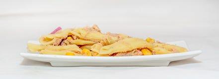 煮熟的面团用红洋葱、金枪鱼和玉米,白色板材 免版税库存照片