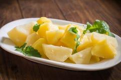 煮的土豆用火箭沙拉 木背景 顶视图 特写镜头 免版税库存照片