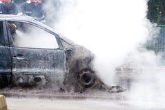 熄灭一辆闷燃的和被烧的汽车的消防员 库存图片