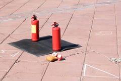 熄灭的火立场两个红色金属大手工二氧化碳或粉末灭火器在黑橡胶 免版税图库摄影