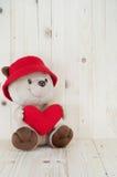 熊在爱穿戴红色帽子举行红色心脏 免版税库存照片