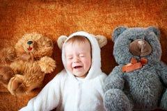 熊服装的小婴孩有长毛绒的戏弄 免版税图库摄影