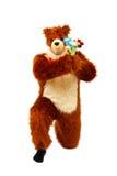 熊服装的滑稽的人有玩具花束的开花 免版税库存照片