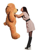 熊美丽的女孩亲吻的玩具 免版税库存照片