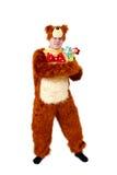熊衣服的幽默人与在白色隔绝的玩具花 库存照片