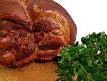 熏制的火腿一个大片断在用绿色植物装饰的一个木板的 肥胖高蛋白高卡路里食物 真正的人的口味 免版税库存图片