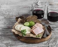 熏制的猪肉、乳酪和两杯在轻的土气木背景的红葡萄酒 库存照片