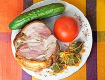 熏制的猪肉和菜在一块白色板材 库存图片