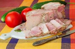 熏制的猪肉和菜在一块白色板材 免版税库存照片