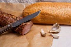 熏制的肉或火腿、刀子、白色麦子面包和大蒜在眉头 免版税库存照片