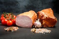 熏制的腌火腿两大块用香料、大蒜和蕃茄 免版税库存图片