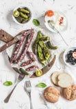 熏制的香肠、烤胡椒、橄榄、乳酪和嫩黄瓜在轻的背景 可口快餐 免版税图库摄影