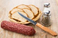 熏制的香肠、面包、盐、胡椒和刀子在桌上 库存照片