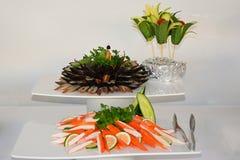 熏制的鱼和螃蟹棍子,装饰用荷兰芹、黄瓜和石灰 库存照片