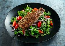 熏制的鲭鱼沙拉用蕃茄,被切的红洋葱,在黑色的盘子的Ruccola 免版税图库摄影